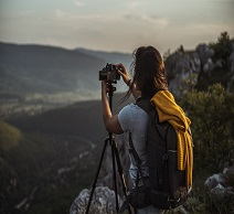 Woman standing in nature and taking a picture